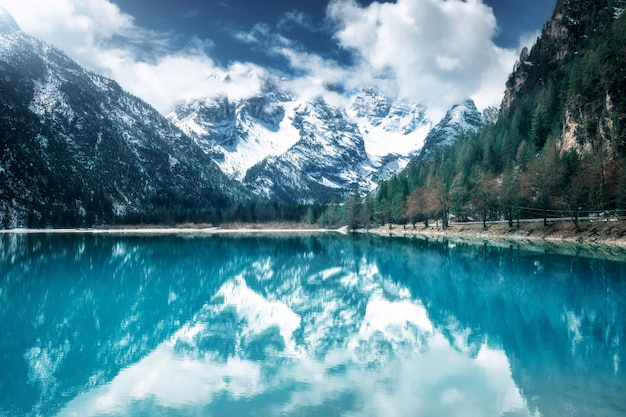 Górskie jezioro z doskonałym odbiciem w słoneczny dzień jesienią. dolomity, włochy. piękny krajobraz z lazurową wodą, drzewa, zaśnieżone góry w chmurach, błękitne niebo jesienią.