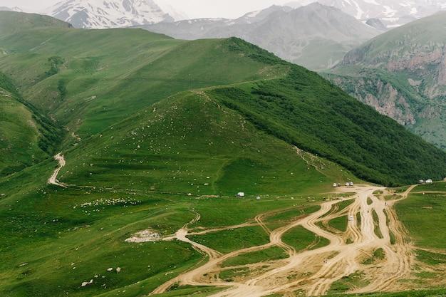 Górskie zielone wzgórza, przejazdy drogowe, samochody. piękny widok na góry gruzji.