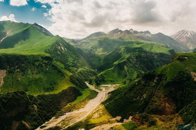 Górskie zielone wzgórza, skrzyżowanie dróg, jasne światło słoneczne na jeziorze. piękny widok na góry gruzji.