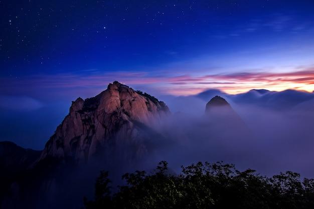 Góry bukhansan pokryte są poranną mgłą i wschodem słońca w parku narodowym bukhansan w seulu w korei południowej.