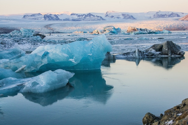 Góry lodowe w pobliżu zamarzniętej wody w zaśnieżonym jokulsarlon na islandii