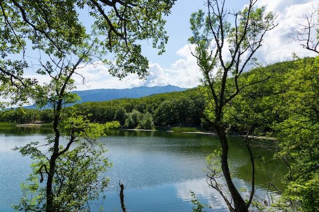 Góry otaczają górskie jezioro. powierzchnia jeziora odbija światło słoneczne. krajobraz