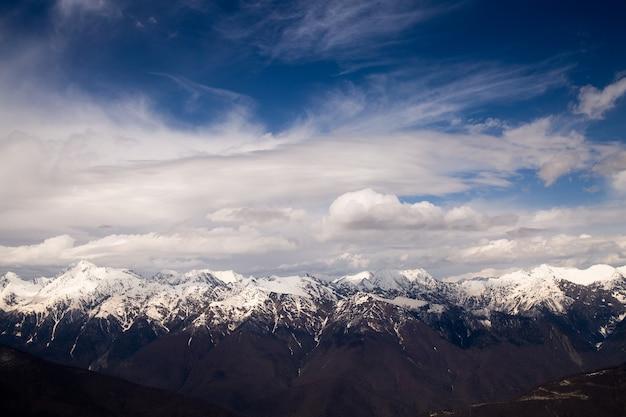 Góry podczas zachodu słońca z mgłą i chmurami oraz ośnieżone góry w alpach