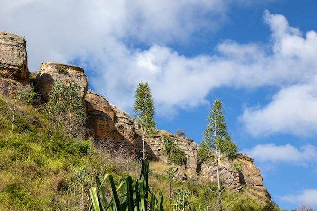 Góry pokryte roślinnością i błękitne niebo z małymi chmurkami