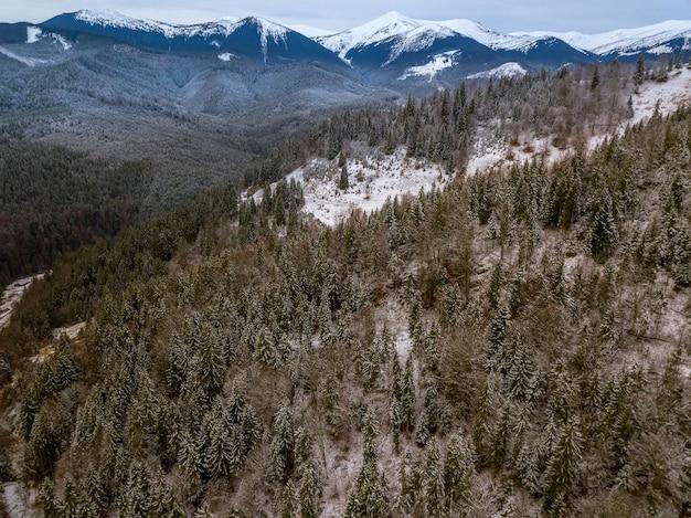 Góry pokryte są lasem. pierwszy śnieg na ziemi i gałęziach. wschód słońca. widok z lotu ptaka