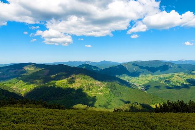 Góry w letni słoneczny dzień z błękitnym niebem i białymi chmurami