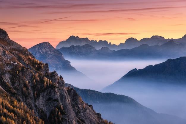 Góry w mgle przy pięknym zmierzchem w jesieni