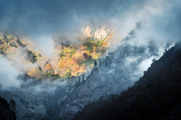 Góry w niskich chmurach w pochmurny wieczór w nepalu. nastrojowy krajobraz z pięknymi wysokimi skałami i dramatycznym zachmurzonym niebem, światło słoneczne, zielony las we mgle o zachodzie słońca. tle przyrody. himalaje