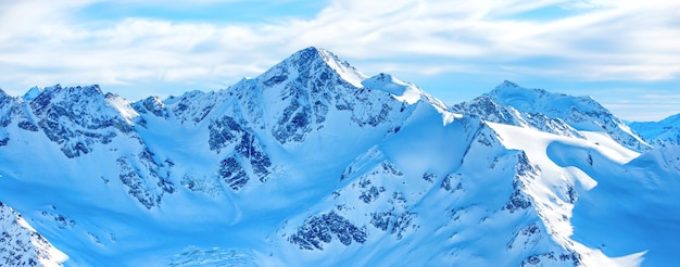 Góry w śniegu. panorama zimowego krajobrazu ze szczytami i błękitnym niebem
