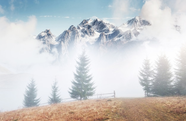 Góry we mgle. szczyty pod ciężkimi chmurami. cichy krajobraz jesień. śnieg na wzgórzach