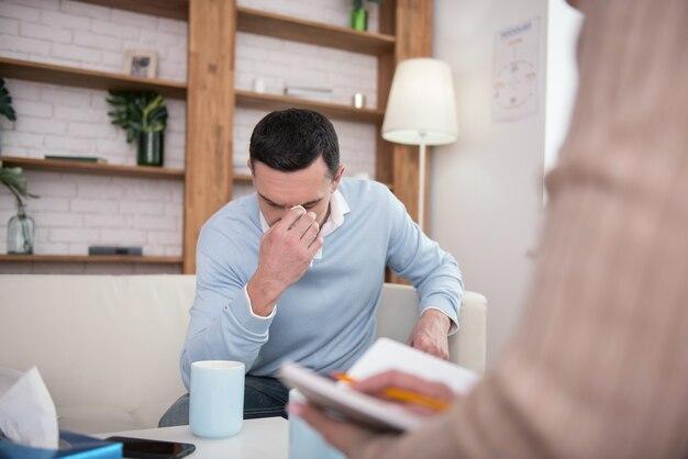 Gorzkie doświadczenie. nieszczęśliwy młody człowiek płacze podczas pozowania na kanapie