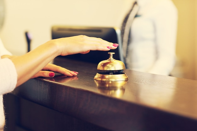 Gość korzystający z dzwonka w recepcji hotelu