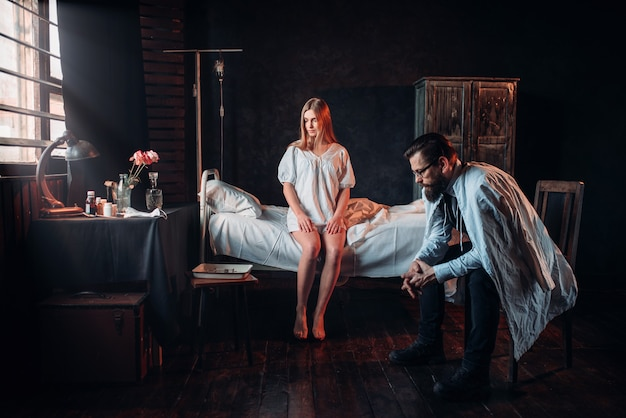 Gość siedzi przed chorą kobietą w szpitalnym łóżku