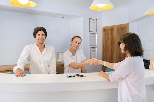 Gość sprawdza w recepcji hotelu, mężczyzn i kobiet powitanie kobiety