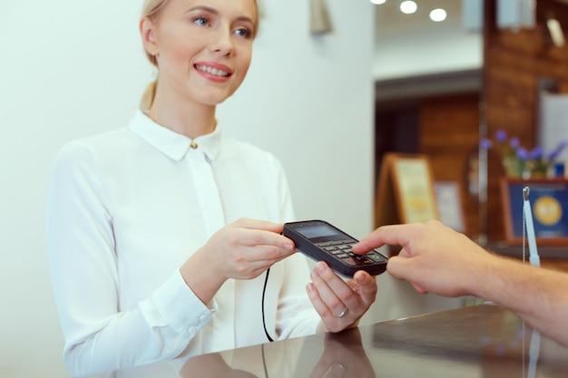 Gość w recepcji hotelu płaci czekiem podczas meldowania