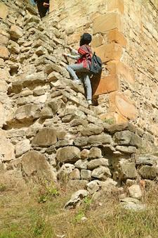 Gość wspina się na wieżę sheupovari w średniowiecznym kompleksie zamkowym ananuri w gruzji