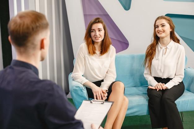 Goście płci żeńskiej siedzą na kanapie. dziennikarz przeprowadzający wywiad. poranne show.