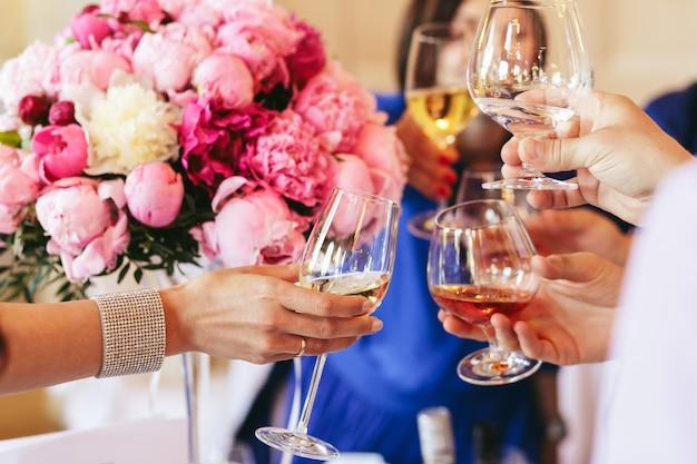 Goście trzymają kieliszki szampana i whisky