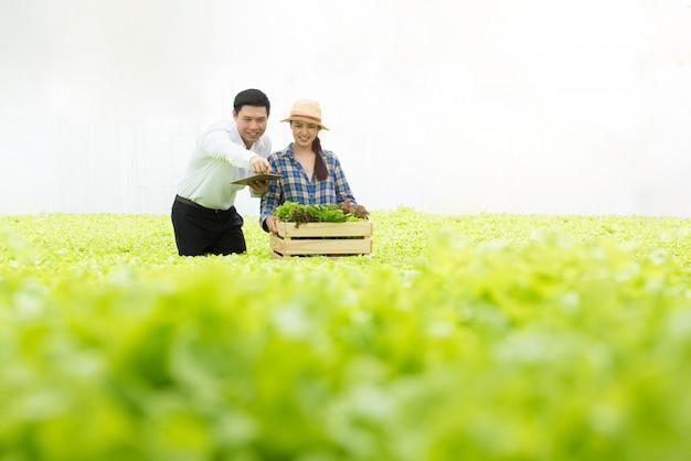 Gospodarstwo ekologiczne warzywa, azjatyckie kobiety rolnicy sprawdzają organiczne warzywa w gospodarstwie