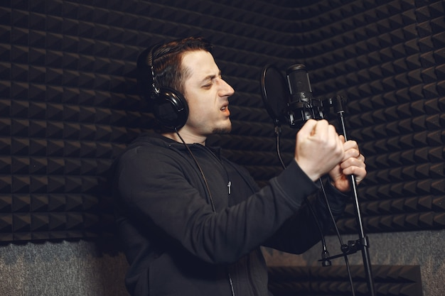 Gospodarz radia gestykuluje podczas nagrywania podcastu w studiu radiowym.