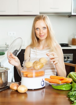 Gospodyni domowa gotowania ziemniaków z parowcem elektrycznym