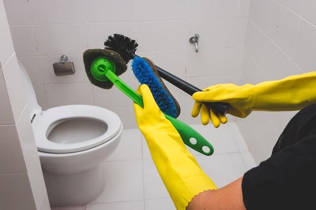 Gospodyni domowa jest ubranym żółtej gumowej rękawiczki pokazuje muśnięcia dla czyścić w toalecie