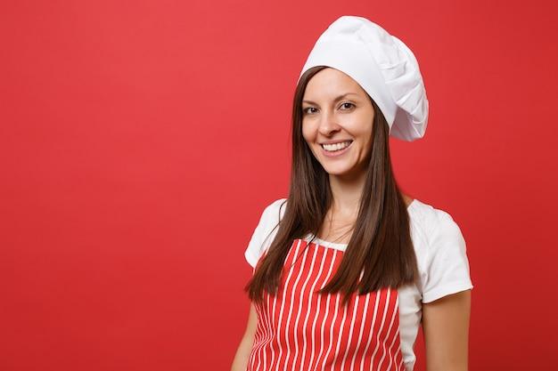 Gospodyni domowa kobieta kucharz lub piekarz w czerwony pasiasty fartuch, biała koszulka, kapelusz kucharzy toczek na białym tle na tle czerwonej ściany. bliska portret brunetka dama gospodyni. makieta koncepcja przestrzeni kopii.