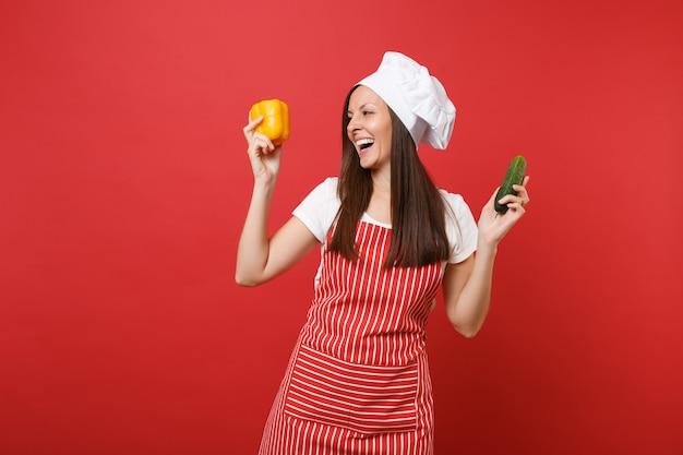 Gospodyni domowa kobieta kucharz lub piekarz w pasiasty fartuch, biała koszulka, kapelusz kucharzy toczek na białym tle na tle czerwonej ściany w studio. kobieta trzyma żółtą paprykę, zielony ogórek. makieta koncepcja przestrzeni kopii.