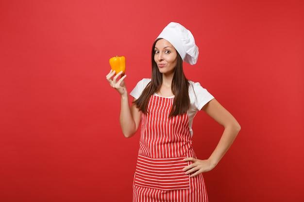 Gospodyni domowa kobieta kucharz lub piekarz w pasiasty fartuch, biała koszulka, kapelusz kucharzy toczek na białym tle na tle czerwonej ściany w studio. uśmiechnięta kobieta trzymać w ręku żółta papryka. makieta koncepcja przestrzeni kopii.