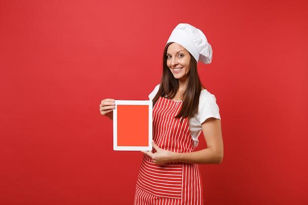 Gospodyni domowa kobieta kucharz lub piekarz w pasiasty fartuch biały t-shirt toczek kucharzy kapelusz na białym tle na tle czerwonej ściany. kobieta trzyma pusty ekran komputera typu tablet dla treści promocyjnych makieta koncepcji przestrzeni kopii