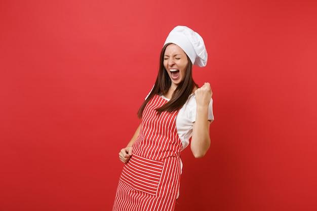 Gospodyni domowa kobieta kucharz lub piekarz w pasiasty fartuch biały t-shirt toczek kucharzy kapelusz na białym tle na tle czerwonej ściany. szczęśliwa ekspresyjna kobieta robi gest zwycięzcy, mówiąc tak. makieta koncepcja przestrzeni kopii.