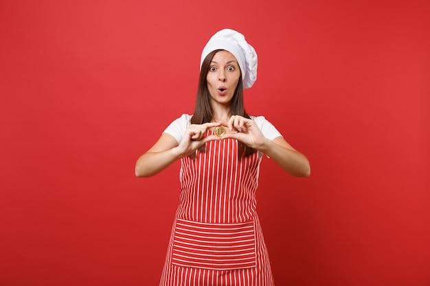 Gospodyni domowa kobieta kucharz lub piekarz w pasiasty fartuch biały t-shirt toczek kucharzy kapelusz na białym tle na tle czerwonej ściany. uśmiechnięta kobieta trzyma bitcoin, bitowa waluta przyszłości. makieta koncepcja przestrzeni kopii.