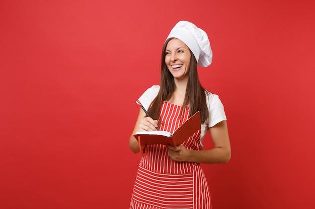 Gospodyni domowa kobieta kucharz lub piekarz w pasiasty fartuch biały t-shirt toczek kucharzy kapelusz na białym tle na tle czerwonej ściany. uśmiechnięta kobieta trzymaj notatnik przepis książkę kucharską i pióro. makieta koncepcja przestrzeni kopii.