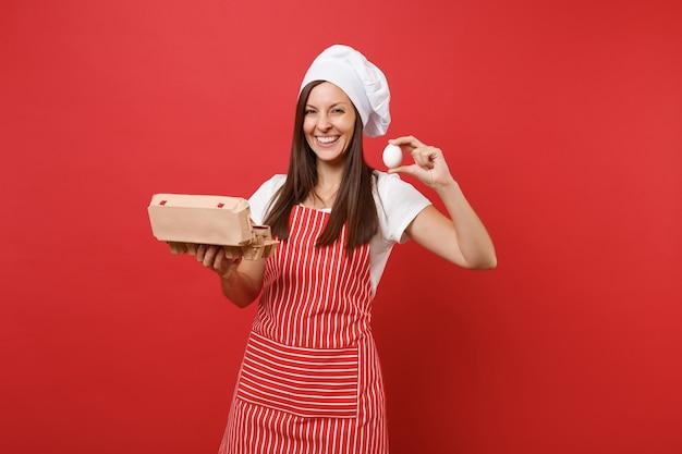 Gospodyni domowa kobieta kucharz lub piekarz w pasiasty fartuch t-shirt toczek kucharzy kapelusz na białym tle na tle czerwonej ściany. kobieta trzyma brązowy rzemieślniczy kartonowy pojemnik na jaja kurze. makieta koncepcja przestrzeni kopii.
