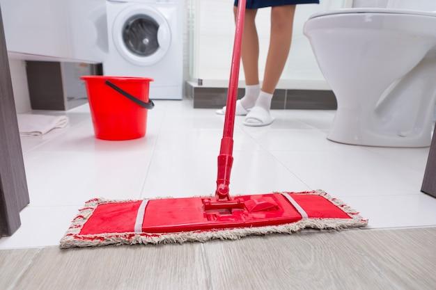 Gospodyni domowa myje podłogę w łazience pod niskim kątem, z bliska widok kolorowego czerwonego mopa i jej stóp z tyłu