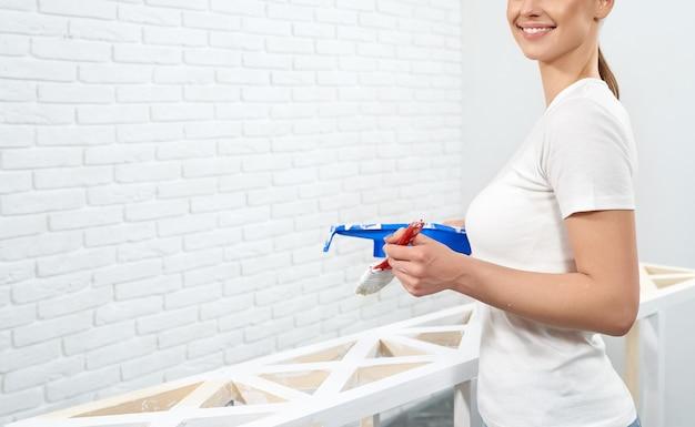 Gospodyni domowa odświeżająca drewniane półki z białą farbą
