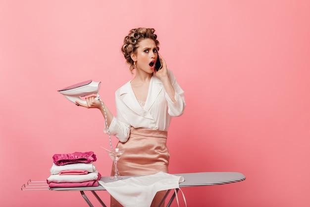Gospodyni domowa plotkuje na telefon i trzyma żelazko na różowej ścianie