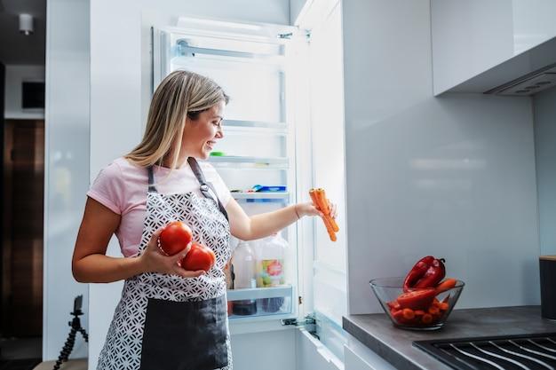 Gospodyni domowa trzyma warzywa i przygotowywa lunch.
