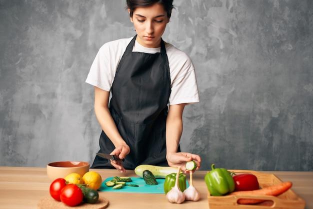 Gospodyni domowa w kuchni cięcia warzyw na białym tle. zdjęcie wysokiej jakości
