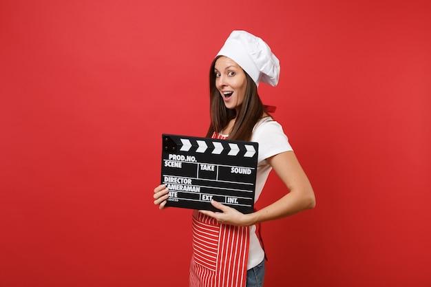Gospodyni domowa żeński kucharz lub piekarz w pasiasty fartuch, biała koszulka, kapelusz kucharzy toczek na białym tle na tle czerwonej ściany. kobieta trzyma klasyczny czarny film co clapperboard. makieta koncepcja przestrzeni kopii.