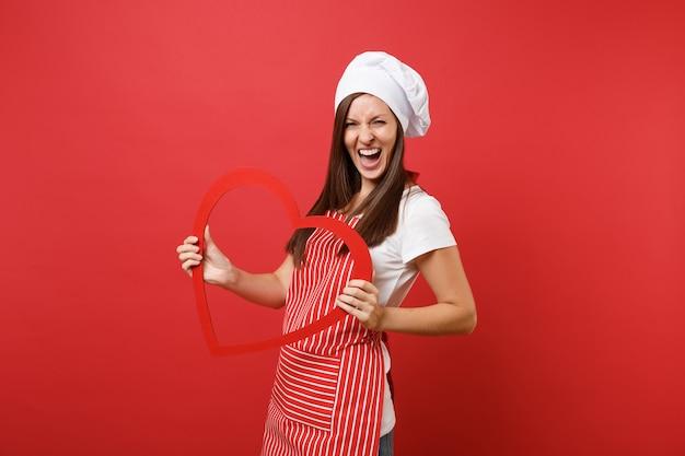 Gospodyni domowa żeński kucharz lub piekarz w pasiasty fartuch, biała koszulka, kapelusz kucharzy toczek na białym tle na tle czerwonej ściany. uśmiechnięta kobieta gospodyni gospodarstwa drewniane czerwone serce. makieta koncepcja przestrzeni kopii.