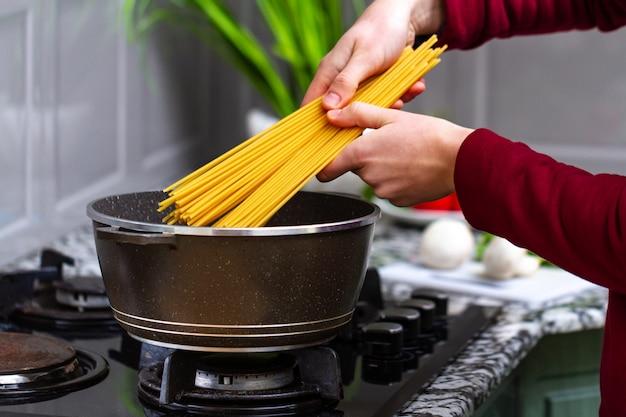 Gospodyni gotuje spaghetti w rondlu na lunch w domu