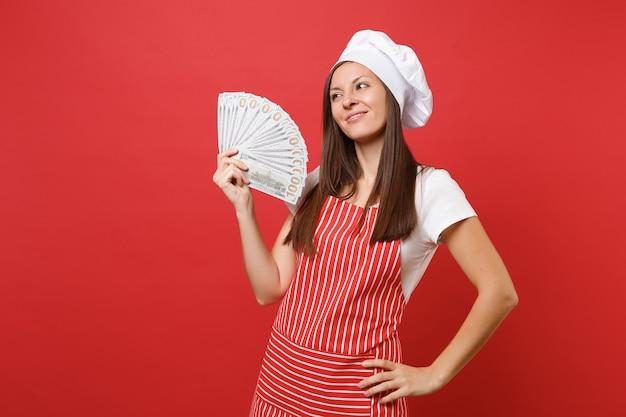 Gospodyni kobieta kucharz kucharz piekarz w pasiasty fartuch, biała koszulka, kapelusz kucharzy toczek na białym tle na tle czerwonej ściany. szczęśliwa kobieta trzyma dużo pieniędzy banknotów dolarów gotówki. makieta koncepcja przestrzeni kopii.