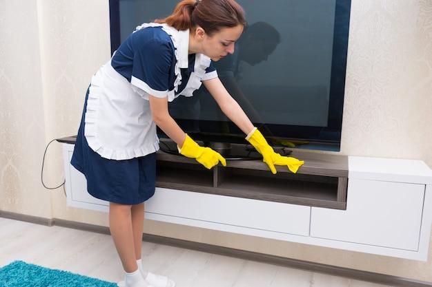 Gospodyni lub pokojówka czyszcząca szafkę pod dużym telewizorem w mundurze z fartuchem i jasnożółtymi rękawiczkami