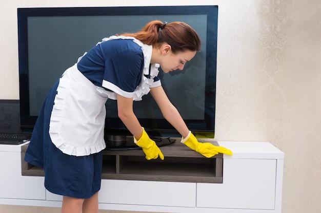 Gospodyni, pokojówka lub gospodyni w schludnym mundurze i białym fartuchu odkurza telewizor i szafkę w mieszkaniu lub apartamencie hotelowym