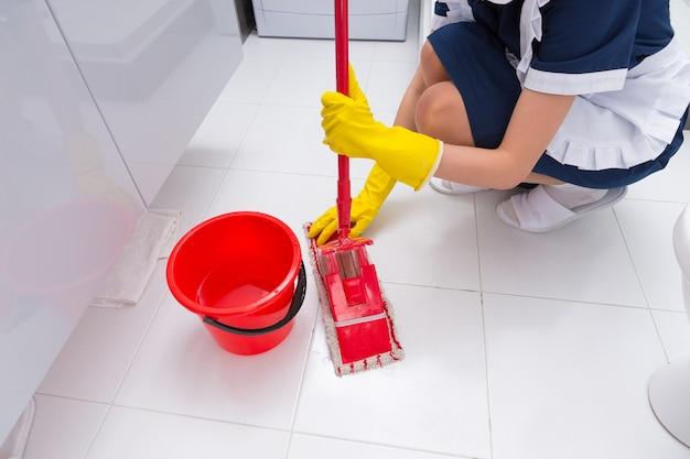 Gospodyni przymocowuje czystą szmatkę do mopa, gdy czyści podłogę w wyłożonej białymi kafelkami łazience w domu lub hotelu