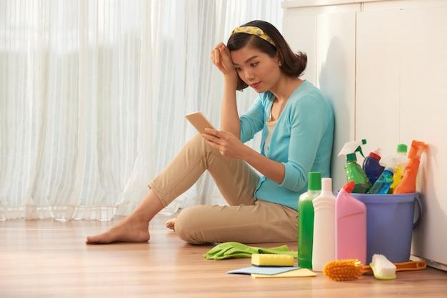Gospodyni siedzi na podłodze w kuchni, robiąc sobie przerwę w pracach domowych i używając smartfona