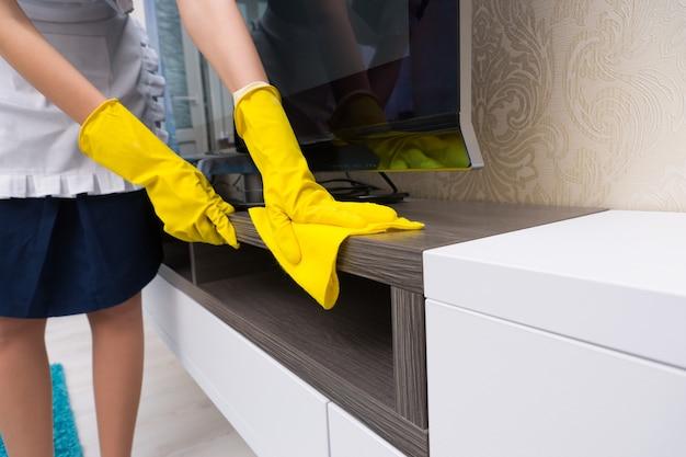 Gospodyni sprzątająca i odkurzająca szafkę telewizyjną kolorową żółtą szmatką, zbliż ręce w żółtych gumowych rękawiczkach