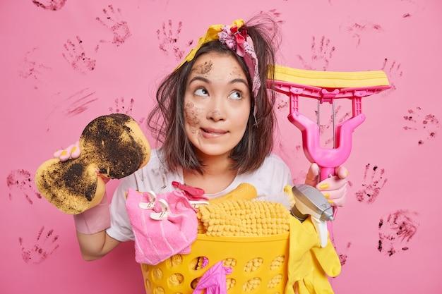 Gospodyni trzyma brudną gąbkę i mop dba o czystość w domu, zamyślona, stoi w pobliżu pełnego kosza na pranie, odizolowanego na błotnistym różu