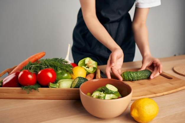 Gospodyni w czarnym fartuchu gotuje w kuchni sałatkę witaminową